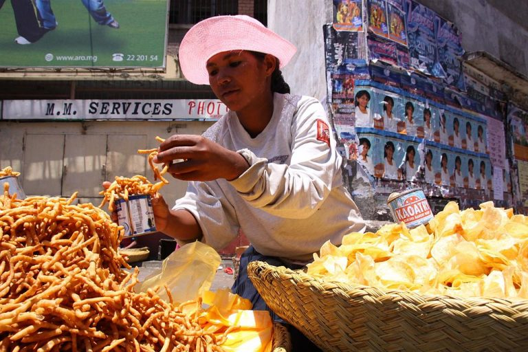A Merina woman selling kaka pizon in Antananarivo, Madagascar. Photo source: Salym Fayad on Wikimedia Commons