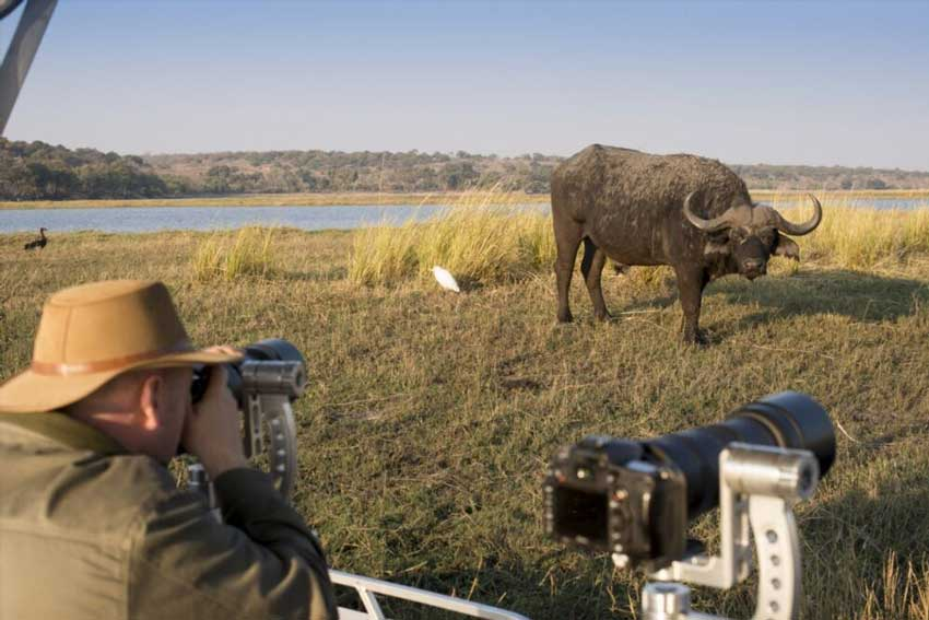 A photo-crazed traveller in action on one of andBeyond's photographic safaris in Botswana – courtesy of andBeyond